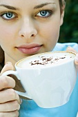 Young woman holding a cup of cappuccino