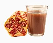 Glass of pomegranate juice and halved pomegranate