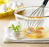 Aufgeschlagene Eier mit Schneebesen in einer Schüssel