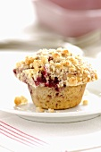 A cherry muffin with crumble topping