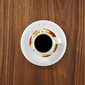 A cup of coffee, partly spilt into saucer