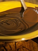 Melted chocolate with wooden spoon in a dish