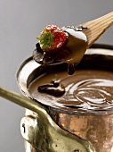 Strawberry in melted chocolate on a wooden spoon