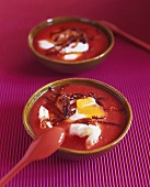 Tomato soup with poached eggs and strips of bacon