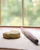 Kuchenteig mit Nudelholz vor einem Fenster
