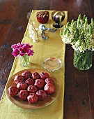 A bowl of pomegranates on a table with vases of flowers