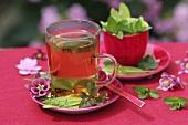 A glass of lemon balm tea with sugar crystals
