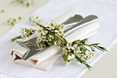 Napkin with cutlery & small posy of Geraldton wax flowers