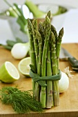 Bundle of asparagus on wooden board, vegetables in background