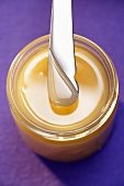Creamy honey in a jar with a knife