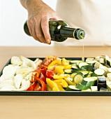 Roasted vegetables: pouring olive oil over vegetables