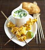 Chicken kebabs with raita and naan bread