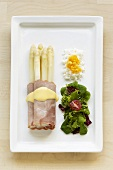 White asparagus wrapped in ham, salad leaves & chopped egg