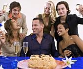 Leute beim Feiern mit Kuchen und Sekt