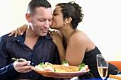 Woman kissing man at table