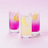 Three glasses of soft drinks with lemon
