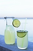Lime drink in bottle and glass with straw