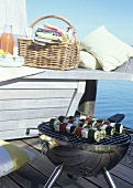 Picnic basket and barbecue on a landing stage