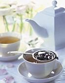 Teetasse mit aufgebrühtem Tee und Teesieb