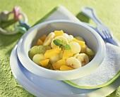Fruit salad: melon, grapes, banana and peach