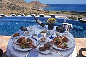 Two plates of spiny lobster on laid table on terrace