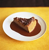 A piece of chocolate cheesecake with chocolate sauce