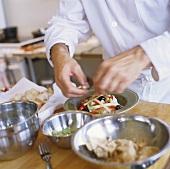Chef preparing a dish of mixed salad