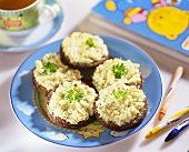Scrambled egg with herbs on pumpernickel rounds