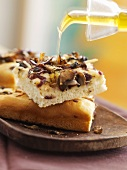 Drizzling focaccia with olive oil