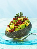 Stuffed avocado with dried tomatoes and pink pepper