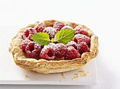 Raspberry tart with puff pastry case and icing sugar