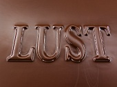 The word 'Lust', chocolate-coated