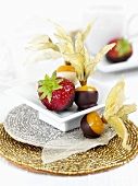 Chocolate-coated physalis and strawberries