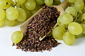 Grapes and grape seeds in a wooden scoop