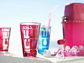 Farbige Gläser mit Eiswürfel und Ice crusher