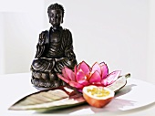 Half passion fruit & water lily in front of Buddha statuette