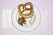 A pair of Weisswurst (white sausages), mustard & pretzel on plate