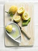 Whole lemon and squeezed lemon halves with lemon squeezer