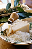 Parmesan, a piece & grated, in a deep plate with cheese knife