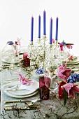 Festlich gedeckter Tisch mit Blumendeko und Kerzenleuchter