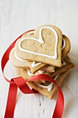 Pile of gingerbread hearts with red ribbon