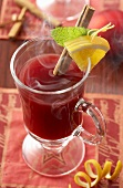 A glass of punch with cinnamon stick and lemon