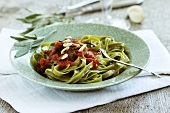 Spinach pasta with fried sage leaves in tomato sauce