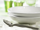 Two white soup plates with spoons