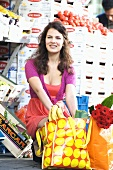 Young woman with shopping bags in front of a vegetable stall