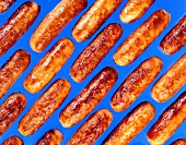 Fried sausages on blue background