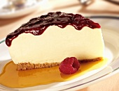 A slice of cheesecake with fruit sauce