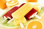 Vanilla ice cream with red fruit coating & orange ice lollies