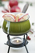 White chocolate fondue with cinnamon apples on sticks