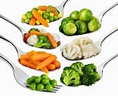 Verschiedene Gemüse auf Löffel und Gabeln